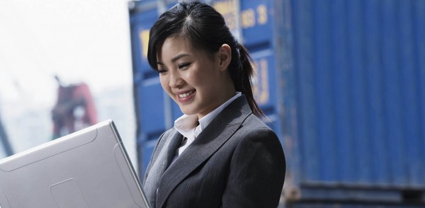 CILT Women in Logstics and Transport - Lady holding a laptop in a shipping port with containers.